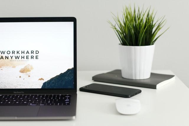 ordinateur posé sur une table blanche, un téléphone, une souris et une plante à droite